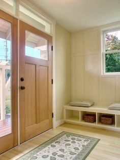 Very nice simple clean lines in this front entry with transom windows at the top and a side light window.  The small built-in for shoes just inside the door is an added touch.