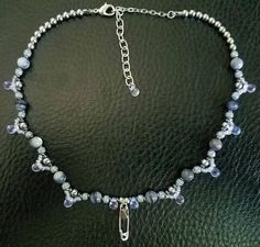 Stormy blue-gray shell beads and seed beads in gray and navy blue make up the majority of this necklace. Between them are the shiny silver beads, and below them dangle tiny irridescent seed beads and glass rain droplets. At the very center hangs a silver safety pin decorated with a tiny silver rain drop. This choker is 14 inches, adjustable up to 16 inches. Proceeds benefit Emilys List:  http://emilyslist.org/  Our vision is a government that reflects the people it serves, and ...