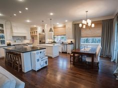 A closer look into the kitchen shows the 2 islands, beautiful wood floors, and eat-in breakfast area off the kitchen as well as the additional seating at the breakfast bar.