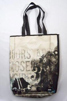 """Bolso Doors Dogo de color negro y beige. Diseño con estampado """"Doors are closed"""", dos asas medianas y dos bolsillos internos."""