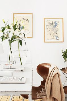 White, serene workspace with throw blanket and fresh flowers.