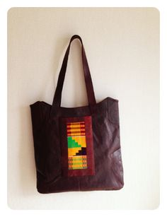 This beautifully hand crafted brown leather tote bag, made with genuine hand woven kente cloth from Ghana.  Each bag is produced using good quality leather and lined with a bright vibrant contrasting African print.  It carries your purse, mobile, keys and other essential items and is a great little everyday shopping bag.