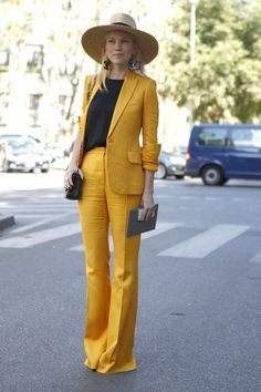 A bold mustard suit, extra-wide brimmed fedora and statement @CHANEL earrings - this impeccable dresser proudly flaunts her style! WGSN Street Shot, Milan Mens Fashion Week, Spring/Summer 2014