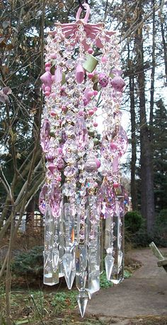 A breathtaking wind chime in the prettiest shades of pink and green, with lots of antique crystal prisms!    Measures 5 across and 19 long.
