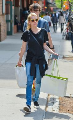 Emma Roberts wears a black t-shirt, patchwork jeans by Black Orchid, slip on sneakers, and a sweater tied around the waist