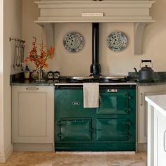 AGA cast iron range in British Racing Green with white cabinets and orange accents. Lovely! www.aga-ranges.com #castironcooking #radiantheat Other notes: Country kitchen with painted units and Belfast sink