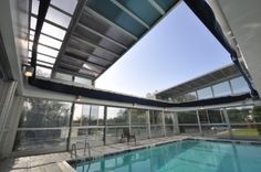 Roll-A-Cover's Retractable Pool Cover at Holiday Inn Express in Milford, CT. Guests can swim year-round under this retractable skylight and rolling wall system. Retractable Pool Cover, Pool Enclosures, Roofing Systems, Skylight, Still Image, Sunroom, Swimming Pools, America, Outdoor Decor