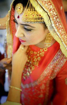 Stunning antique gold jewelry on an Indian bride. Lovely paasa / jhoomar and teeka. Pretty orange lehenga.