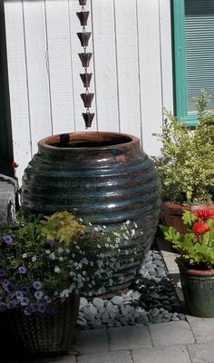 Love the idea of having a rain chain hung above a large pottery urn!