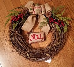 Grapevine Christmas wreath with burlap bow,  pinecones and noel.