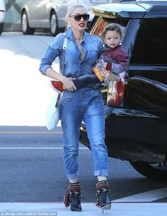 On the go: The star, who carried her youngest son, Apollo, left a few buttons of her jumps...