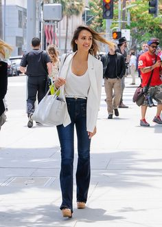 Jessica Alba wears a white tank, blazer, flare jeans, a white satchel, and platform sandals