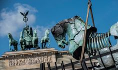 One of the 20 'pop-up' horse sculptures is installed in front of the Brandenburg Gate in Berlin.