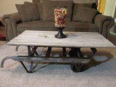 100% Recycled Coffee Table- antique hand truck / dolly with a reclaimed barnwood top.  www.rusticforgeinteriors.com