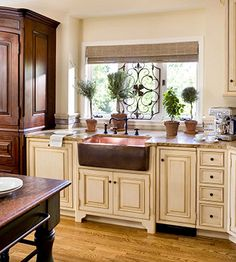 Even though most of my dream kitchen embraces warm mahogany cabinetry, I love the creamy glazed kitchen sink area. A copper farmhouse sink with a spectacular view makes washing dishes therapeutic!