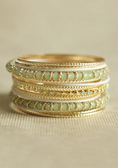 Kyoto Garden Bangle Set 16.99 at shopruche.com. Enhance any outfit with this elegant set of fifteen gold-toned bangles featuring glistening mint-hued stones and ivory accents.2.75� diameter