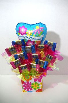 Arrangement includes 12 Ghirardelli Spring Assortments: Dark & Sea Salt Caramel and Dark & Raspberry Mix in a colorful container with a Happy Mother's Day Balloon. No delivery on Saturday or Sunday. A