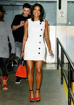Gabrielle Union wears a white shift dress, colorful suede wedges, and a suede tote