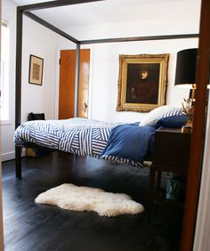 minimalist four poster bed. navy, white, and gold bedroom