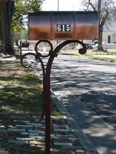 Forged mailbox stand using traditional elements of buttonhead scrolls and wrought iron collars.