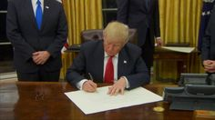 The Trump administration's interior design changes to the Oval Office came into view for the first time Friday when the newly inaugurated president invited the press in as he signed his first executive order. Gone are the deep red curtains that hung in the office during the Obama presidency, replaced by bright gold curtains reminiscent of Trump's apartment inside Trump Tower.