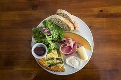 Kampin Fleuristesta saa pöytiin brunssilautasia. Tässä muun muassa parsapiirakkaa, hunajamelonia, ilmakuivattua kinkkua, juustoja ja pikkukuppi tapenadea.