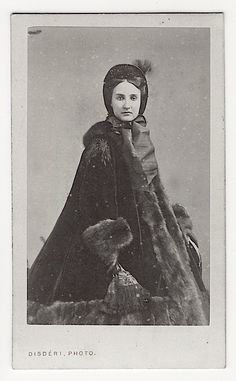 Expanding skirts created a need for appropriate outerwear. One answer was a conical coat or paletot.; this is a great example of a paletot.She also wears a bonnet, but it is very diminutive compared to those worn in the 1830s or 1840s.While the silhouette is conical, it is hard to give an accurate date because the cone is formed by the paletot while the shape of the skirt below is unknown.