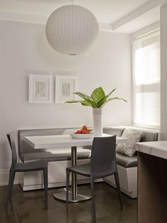 Sleek gray and white banquette seating in a small eat-in area.