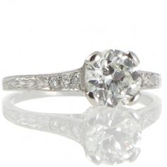 An Art Deco solitaire ring made in platinum with a central 0.89ct old cut diamond graded as colour J-K clarity SI1 set in four claws that taper down the pierced gallery highlighted by millegrain detailing all between a pair of upswept shoulders set with 3 small diamonds each tapering down to the partially engraved band. Total Diamond Weight: 0.96ct Band Width: 1 - 1.9mm Weight: 2.4grams