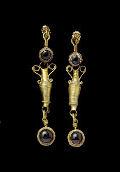 Gold and garnet Hellenistic earrings in the form of amphorae, c. 2nd-1st century BCE. From Bonhams auction house.
