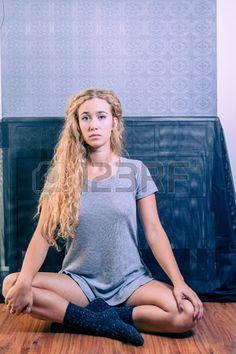 Cute blue eyed American female sitting on floor Stock Photo