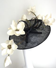 Black sinamay saucer with branch of white magnolia flowers and a black sinamay bow