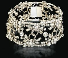AN EXQUISITE ANTIQUE DIAMOND CHOKER, BY A.E. KÖCHERT   Of openwork floral motif, designed as a series of collet-set diamond flowerheads and old-cut diamond leaves, the centre accented by interlocking diamond links, to the slightly scalloped diamond border with diamond collet detail, circa 1890, 34.0 cm long, in a fitted Köchert brown leather case  By A.E. Köchert