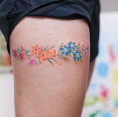 Colorful floral garter tattoo by Tattooist River
