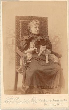 Victorian lady with cats—young sibling cats from the look of it!
