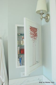 Medicine cabinet in the wall behind art