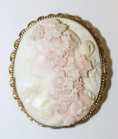 Shell cameo brooch depicting a bacchante, in a gold ropetwist mount, stamped '9ct', brooch length 5.5cm.