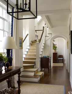The traditional entry hall and staircase feature sisal carpeting and dark wood floors | archdigest.com
