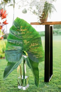 A large anthurium leaf serves as a creative menu display. Elegant, gold calligraphy shines against the vibrant green hues and contrasts with the leaf's jungle vibes.