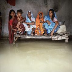 A drowning World ~ Bihar, India: Urmila Devi, Sangeeta Devi, Marni Devi and Nago Devi sit on a bed above floodwaters in the village of Chajan Mania near Muzaffarpur. Fishing communities are usually some of the most vulnerable people in times of floods as they live close to rivers Photograph: Gideon Mendel