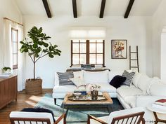 Lauren Conrad's cozy living space with a vintage blue rug, a white sectional, matching white midcentury modern chairs, and a large indoor plant