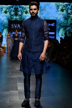 SVA BY SONAM & PARAS MODI Men Featuring a midnight blue bundi jacket in raw silk base with cutdana and thread work embroidery. It is paired with a contrasting blue kurta in organza base and pants. Indian Men Fashion, Indian Fashion Designers, Mens Fashion Suits, Wedding Dresses Men Indian, Wedding Dress Men, Modi Jacket, Designer Clothes For Men, Designer Jackets, Men Clothes