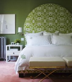 Bedroom with matcha-esque colored wallpaper and bed frame.