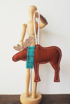 This dapper moose prefers to wear a scarf to keep his neck warm during the cold winter months.    - Hand cut and sewn using brown, wheat and red Merino wool felt, a renewable quality fiber that is soft, yet durable  - Gently stuffed with polyester filling for shape  - Loop of white cotton cording firmly attached for easy hanging  - Moose measures 5 inches by 5 inches (not including loop)    Interested in ordering a moose with wearing a different color scarf? Please contact me via convo - I…