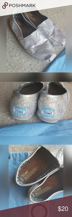 Toms Silver Glitter Shoes 8.5 wide Good Used Condition Silver Glitter Toms. 8.5 wide. I normally wear and 8 but these still fit comfortably. Wear on back heels and some of the glitter has fallen off. No box but dustbag included Toms Shoes Flats & Loafers