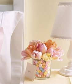 Place a vase within a larger glass cylinder of approximately the same height. Fill the inner vase with flowers, and pour jumbo Conversation Hearts in the space between the two vases.