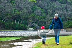 Stock Photo : A toddler holding hands with his grandmother as they walk by a river.
