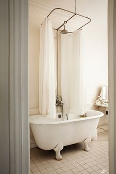Parisian / Paris apartment bathroom with clawfoot tub and shower enclosure with 2 curtains.