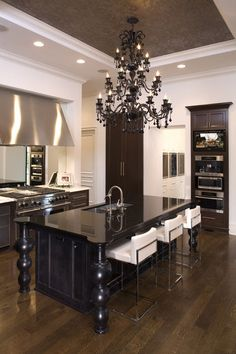 If your kitchen is traditional, this large black chandelier is beautiful against this large black kitchen island.  What a stunning fixture!