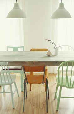 Salle à manger avec table en bois cérusé et ensemble de chaises en bois dépareillées. Harmonie de vert jade, vert céladon et chaises laissées en bois brut